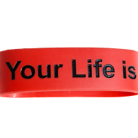 """Red silicone band with debossed text. The text is filled in with shiny black ink. The text reads """"your life is""""."""