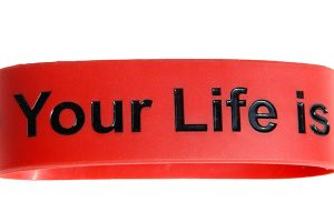 Red silicone band with debossed text. The text is filled in with shiny black ink. The text reads