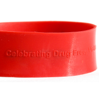 """Red silicone band with raised embossed text. Text matches color of band and reads """"celebrating drug free"""""""