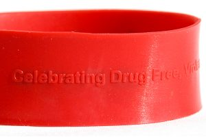 Red silicone band with raised embossed text. Text matches color of band and reads