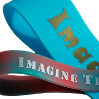 Two silicone bands crossing over each other. One band is a wide teal band with metallic gold print. The other band is a swirl of red and teal with silver print. Both bands have the word imagine visible.